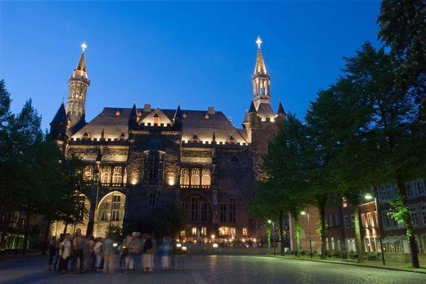 Aachener Rathaus mit Besuchergruppe bei Nacht