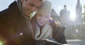Paar vor Aachener Dom mit Broschüre